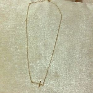 Gold cross necklace. Cross sits facing sideways